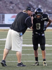 Desert Hills coach Carl Franke talks with quarterback Nick Warmsley during Desert Hills' season opening victory Friday, Aug. 23, 2013, at Thunder Stadium. The Thunder defeated Stansbury 12-0. Todd Seifert / The Spectrum