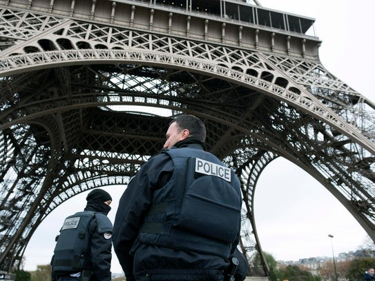 Police forces on patrol pass under the closed Eiffel