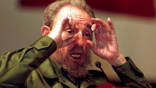 FILE - In this Aug.18, 1999 file photo, Cuba's leader Fidel Castro gestures at a speaking event as he explains that he does not understand why he is not blind after all the camera flashes he has received in Havana, Cuba. Former President Fidel Castro, who led a rebel army to improbable victory in Cuba, embraced Soviet-style communism and defied the power of 10 U.S. presidents during his half century rule, has died at age 90. The bearded revolutionary, who survived a crippling U.S. trade embargo as well as dozens, possibly hundreds, of assassination plots, died eight years after ill health forced him to formally hand power over to his younger brother Raul, who announced his death late Friday, Nov. 25, 2016, on state television. (AP Photo/Jose Goitia, File)