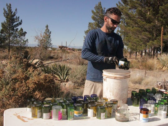 Ryan Timmermans cleans cut bottles at the Foxhole Homes build site on Fiddler's Green in Otero County. The bottles will be used as light-and-heat-conveying bricks in a south-facing cement wall of an Earthship home being built to house a homeless veteran.