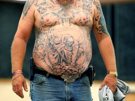 Roger Ryle displays his tattoos to judges at the tattoo