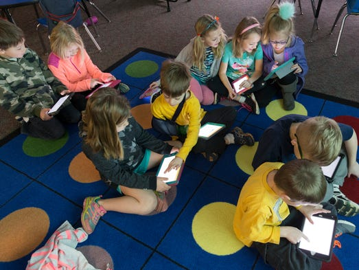 First-grade students use electronic tablets for a lesson