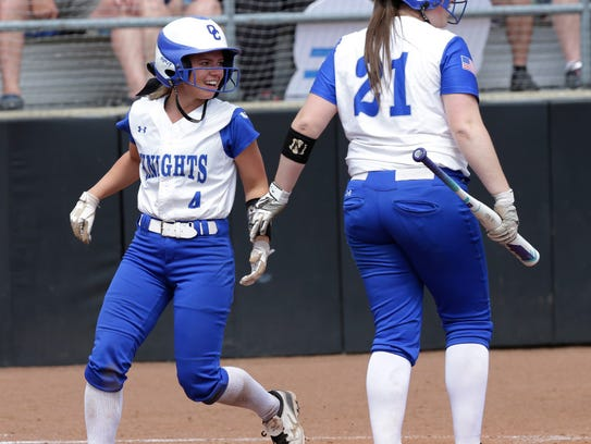 Tori Golden (left) scores a run for Oak Creek during