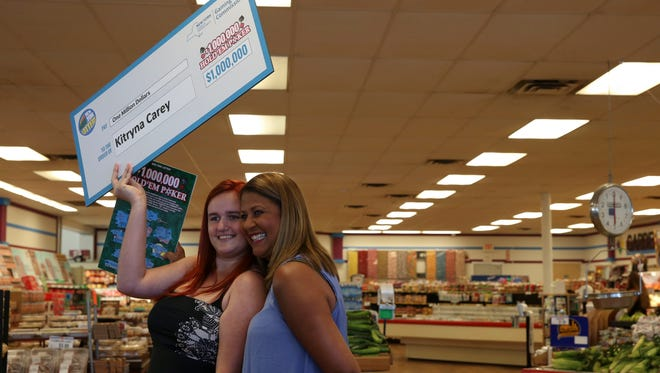 Kitryna Carey, 20 of Hilton holds up her check with Yolanda Vega after winning $1 million playing a New York Lottery instant game in June.