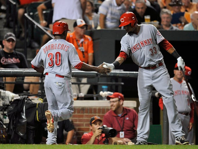 Cincinnati Reds center fielder Jason Bourgeois (30) is congratulated by Yorman Rodriguez (33) after scoring in the third inning against the Baltimore Orioles at Oriole Park at Camden Yards.