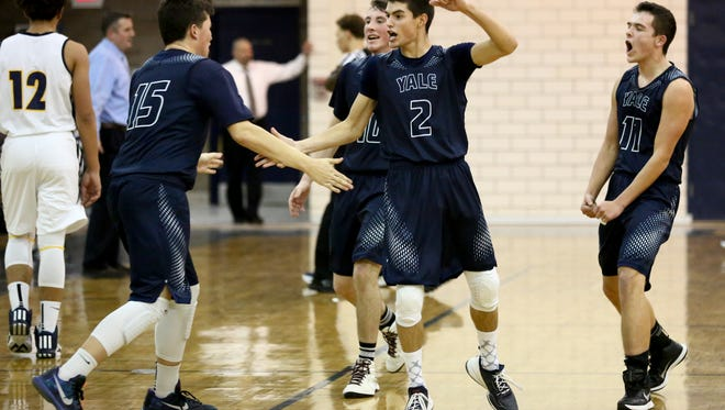 Yale junior Matthew Donnellon, left, sophomore Blake Pilgrim and sophomore Derik Porrett celebrate after scoring streak led to a Northern time out during a basketball game Tuesday, Jan. 5, 2016 at Port Huron Northern High School.