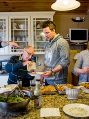 Joe Bonavita grates Parmesan cheese for Joe Frommeyer Jr. (center) as Nick Frommeyer (left), Michelle Eubank (second from right) and Gail Vilardo Frommeyer (far right) serve the pasta course at their family's Sunday dinner in Crescent Springs, Ky. Sunday, February 26, 2017. The family comes together every Sunday for a multi course meal.