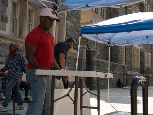 Volunteers Chris Thomas, left, and Larry Lazo set up