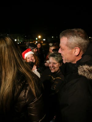 Rob Hecksel chats with friends and family after about 100 people flash mobbed his Lansing home, Tuesday, Dec. 19, 2017, singing Christmas carols for the retired Lansing Fire Department battalion chief and his family. Hecksel has pancreatic cancer, so about 40 of his Lansing Catholic classmates, along with friends, family, police officers, and fellow firefighters teamed up to bring the family joy in their trying time.