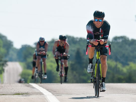 After a swim, athletes take their bikes on the road
