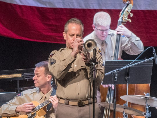 Chief Master Sgt. Kevin R. Burns plays trumpet as the