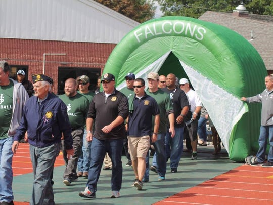 Honorees walk onto the field during St. Joseph High School's Military, Police and Fireman Appreciation Day last season.