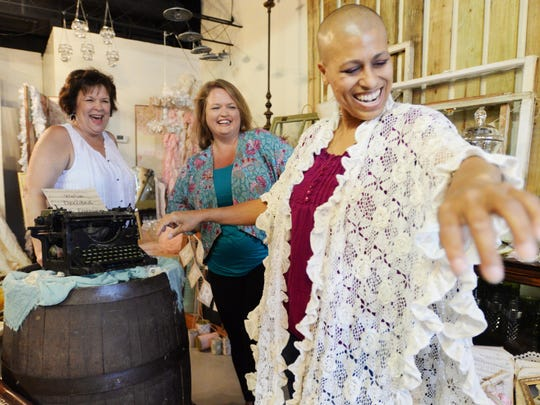 LaTonia Barto tries on a shaw with the help of Susan Nance (left) and Michelle Babin at Vintage Rental Boutique. LaTonia Barto is struggling with her fourth bout of cancer, because of donations from friends in the community she is planning a dream wedding to re-marry Joey Barto.