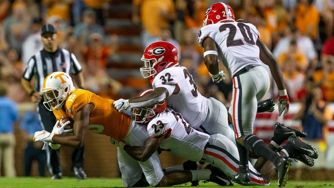 Georgia inside linebacker Monty Rice (32) and Georgia defensive back Mark Webb (23) tackle Tennessee wide receiver Jauan Jennings (15)  in the first half of a NCAA football game between Georgia and Tennessee in Knoxville, Tenn., on Saturday, Oct. 5, 2019.
