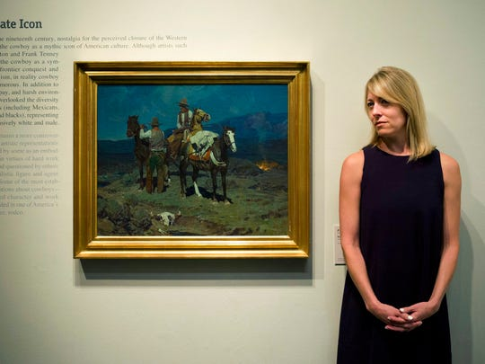 """In this Friday, June 2, 2017 photo, chief curator Amy Scott pauses for photos with a painting titled """"First Streak of Dawn"""" by Frank Tenney Johnson at the Autry Museum of the American West, in Los Angeles."""
