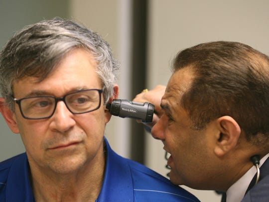 Dr. Alex Fahoury, works with patient Tom Felice at