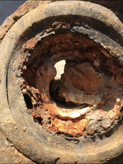 A corroded and clogged water pipe, excavated beneath