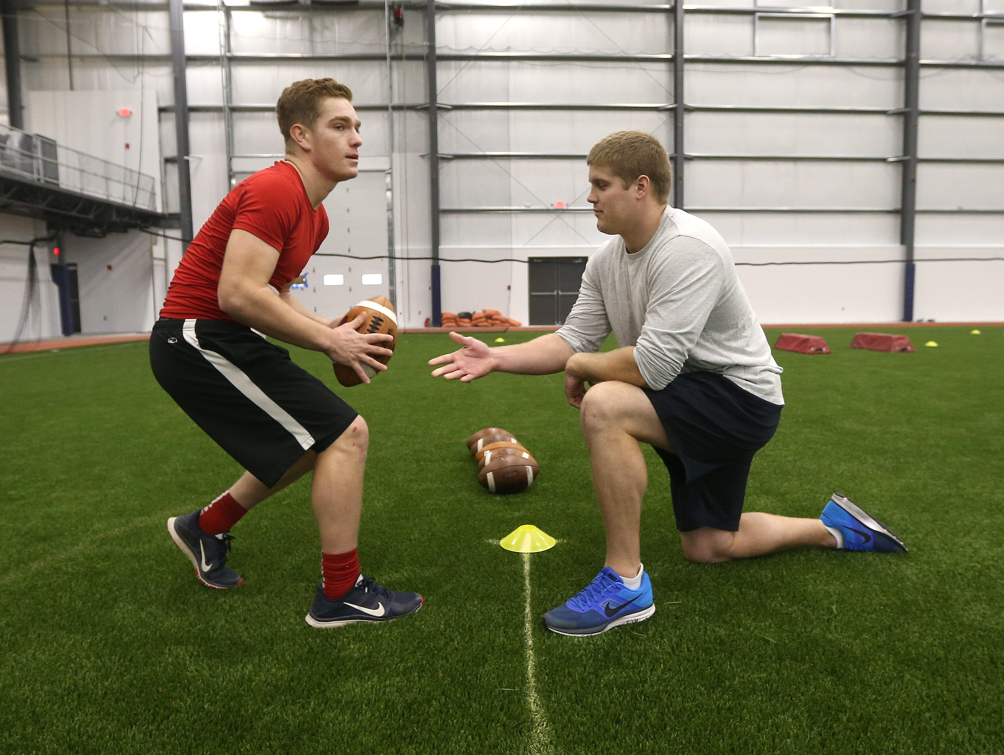 Former NFL player Chris White snaps the ball to Hilton quarterback Johnathan Letta during drills at the AGR Sports Combine at Pinnacle Athletic Campus in Victor.