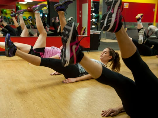 Alexandra Vartanian, of Collingswood, does scissor kicks in a class led by raining manager Derek Cafasso at Retro Fitness in Moorestown on Monday, December 29, 2014.