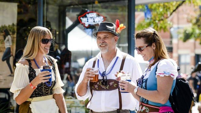 From left, Melinda Kolm, Carl Benvenga and Mae Benvenga enjoy drinks at FORToberfest Saturday, Sept. 20, 2014. This end of summer festival brings together beer, biking, and bands.