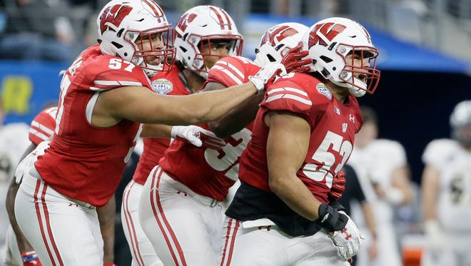 Wisconsin linebacker T.J. Edwards (front) is congratulated by teammates after an interception against Western Michigan in the Cotton Bowl last season.