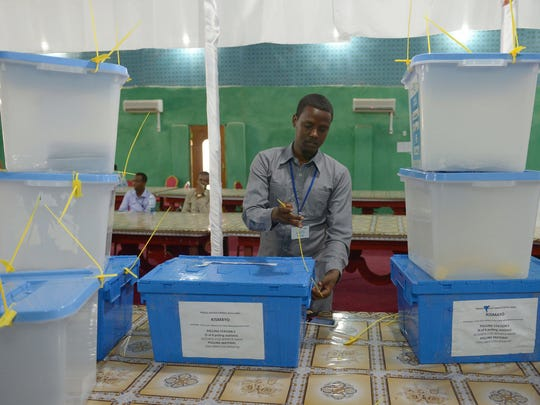 An electoral agent closes ballot boxes with cable ties