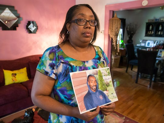 Cynthia Gray Cox, 52, shows a photograph of her brother