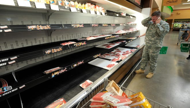 Maj. Ryan Burke scans nearly empty shelves in the meat section Oct, 1, 2013, at the Fort Carson Commissary in Colorado Springs, Colo. The commissary was busier than normal with news that would close indefinitely Tuesday because of the government shutdown.