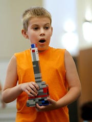 Ryan Savage of Bayville,NJ carries a tower made out of Lego building blocks to the foot drawing of Jerusalem.