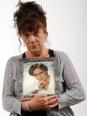 Judy Wilson of Manitowoc poses with a photograph of
