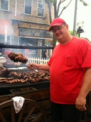 Jerry Girtman, owner of the Red Wood Grill in Commerce Township, cooks up ribs and chicken at Arts, Beats & Eats in this 2014 file photo.