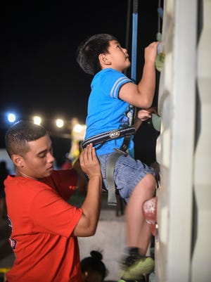 A young thrill-seeker begins his ascent on the rock climbing wall at the Liberation Carnival in Tiyan on June 13.