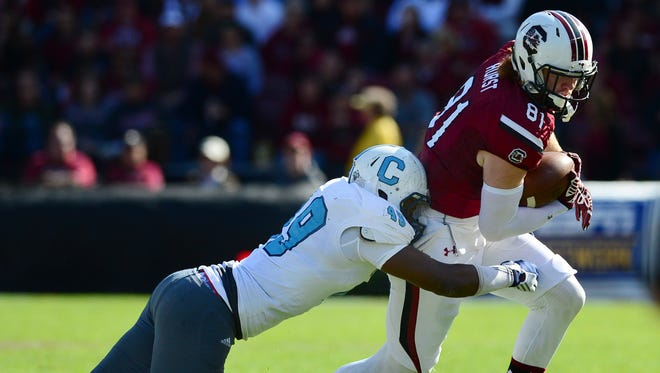University of South Carolina's Hayden Hurst (81) is tackled by The Citadel's James Riley (49) during the second quarter at Williams-Brice Stadium on Saturday.