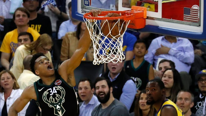 Bucks forward Giannis Antetokounmpo slams one home as Kevin Durant and Warriors fan look on Thursday night in Oakland, Calif.