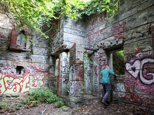 Worker Andrew Schuyler, 24, looks inside the gate house of the former Untermyer property at the gardens of Untermyer Park, Sept. 14, 2012 in Yonkers. A group called the Untermyer Gardens Conservancy is restoring the 45-acre grounds to their former glory. ( Tania Savayan / The Journal News )