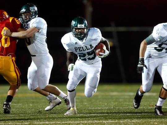 Pella running back Nathan Henry (25) hits a huge hole for big yards against Carlisle in a high school football game at Carlisle High School Friday, October 3, 2014.