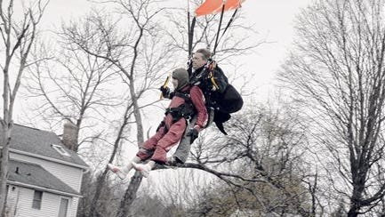 """Eleanor """"Nanny"""" Cunningham, left, with tandem master Dean McDonald, come in for a landing after their skydive in Gansevoort, N.Y, a day after her 100th birthday. It was Cunningham's third jump, after taking up the sport at age 90."""