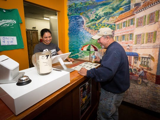 Sandy Ramos totals a bill for customer Alex Rosa at Pastaggios Italian Cuisine and Pizza. Rosa, a local artist, designed the restaurant's mural to his right,