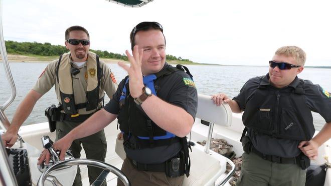 Matt Merrick of the Iowa Department of Natural Resources waves at boaters as he navigates a patrol boat around boats moored at the Saylorville Marina at Saylorville Lake on Saturday, May 23, 2015.