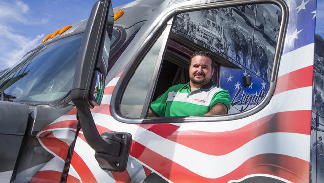 Sean Williams, president of Southwest Truck Driver Training, poses with a semi at the school in Phoenix on Dec. 20, 2016.