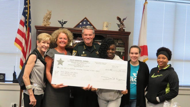 The Escambia County Sheriff's Office donated $292,500 to around 80 local organizations using money forfeited in drug cases. Pictured here are representatives of the Pace Center for Girls receiving a $15,000 check in October.