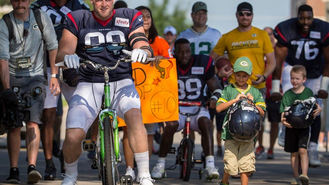 Houston Texans' J.J. Watt rides a bike to a joint NFL football practice between the Texans and the Green Bay Packers Monday, Aug 5, 2019, in Green Bay, Wis. (AP Photo/Mike Roemer)