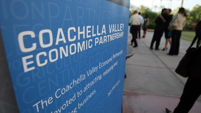 People arrive and walk by signage before the Coachella Valley Economic Partnership's 2010 Economic Summit at the Renaissance Esmeralda Resort & Spa in Indian Wells, Calif.