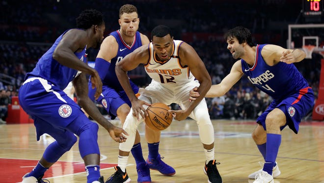 Phoenix Suns' TJ Warren, center, is defended by Los Angeles Clippers' Milos Teodosic, right, Blake Griffin and Patrick Beverley, left, during the first half of an NBA basketball game Saturday, Oct. 21, 2017, in Los Angeles. (AP Photo/Jae C. Hong)