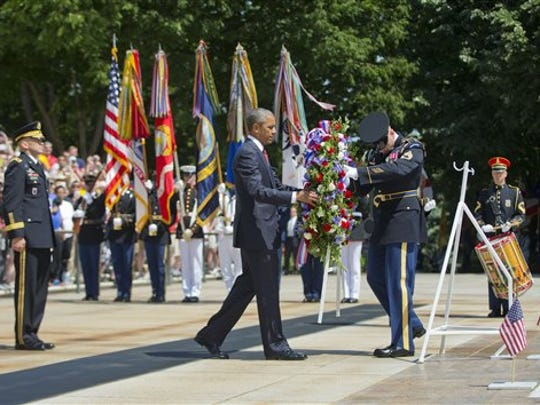 President Barack Obama, accompanied by Maj. Gen. Jeffrey S. Buchanan, left, Commander of the U.S. Army Military District of Washington, and the with the aid of  Sgt. 1st Class John C. Wirth, lays a wreath at the Tomb of the Unknowns, on Memorial Day, Monday, May 25, 2015, at Arlington National Cemetery in Arlington, Va.