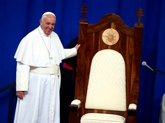 Pope Francis smiles as he looks over a wooden chair made for him by inmates during his visit to Curran-Fromhold Correctional Facility in Philadelphia, Sunday, Sept. 27, 2015.
