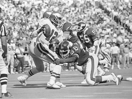 Philadelphia Eagles quarterback Randall Cunningham is sacked by New York Giants Carl Banks as he attempts to pass during third quarter NFL action in Philadelphia, Pa., Sept. 30, 1985. (AP Photo/Rusty Kennedy)