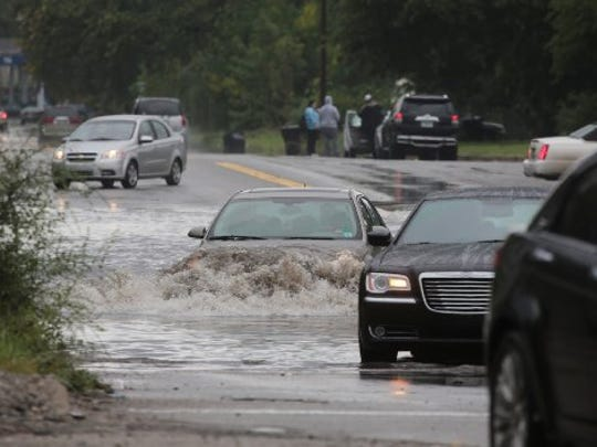 Cars struggle to drive through a flooded section of Oakland Ave. in Highland Park.