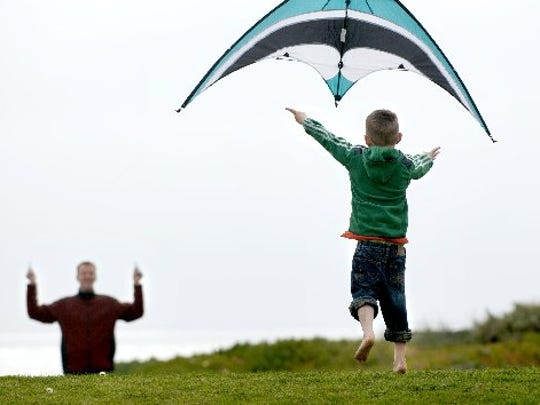 T.J. Scarborough flies a kite with the assistance from his son Luukas Scarborough, 6, at Marina Park in this 2012 file photo.