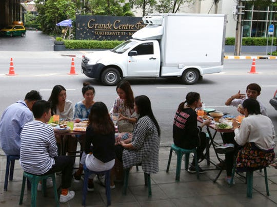 In this April 7, 2017 photo, people have their lunch at a street food shop on Thonglor road in Bangkok, Thailand. Officials see street food as an illegal nuisance and have warned hawkers in Thonglor to clear out by April 17. Efforts by authorities in military-ruled Thailand to impose order on the chaotic capital city have a fresh target: cheap and tasty pad thai. The latest crackdown by Bangkok city officials is going after the vendors whose carts selling everything from Thailand's signature noodles to spicy tom yum goong soup have become institutions on the capital's hot and humid sidewalks.